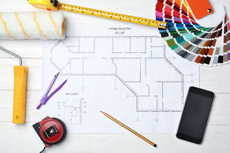 Set of decorator's tools on project drawing, flat lay