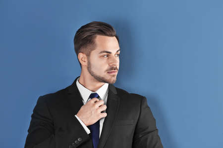 Portrait of young man with beautiful hair on color background