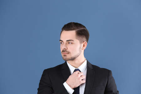 Portrait of young man with beautiful hair on blue background