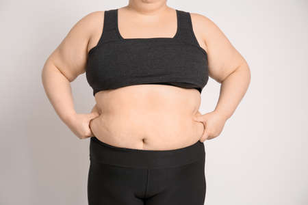 Overweight woman on light background