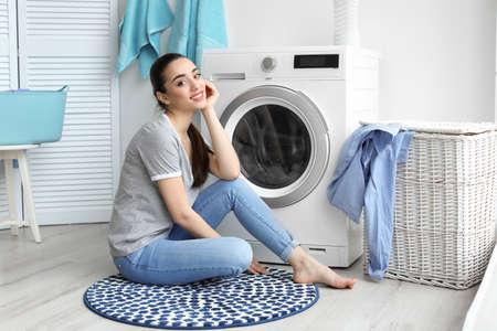Young woman sitting near washing machine in laundry room 版權商用圖片