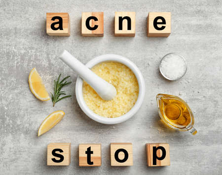 "Wooden cubes with phrase ""Stop acne"" and homemade effective problem skin remedies on grey background, flat lay"