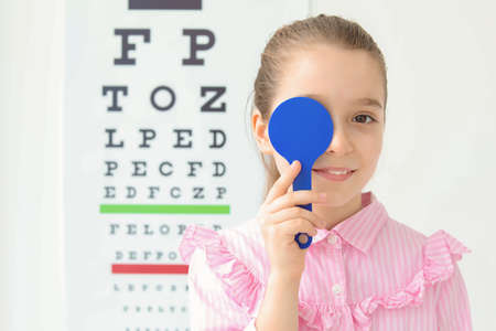 Cute little girl near eye chart in ophthalmologist office