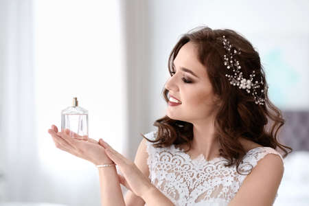Beautiful young bride with bottle of perfume on blurred background Archivio Fotografico