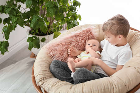 Cute boy with little baby in lounge chair at home 版權商用圖片
