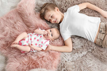 Cute little baby with elder brother lying on soft fluffy plaid at home