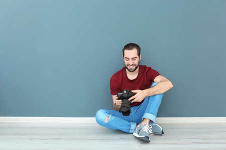 Young photographer with professional camera near color wall