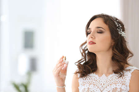 Beautiful young bride with bottle of perfume on blurred background Reklamní fotografie