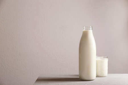 Bottle and glass with milk on table against grey wall Archivio Fotografico