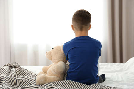 Lonely little boy sitting on bed in room. Autism concept Stock Photo