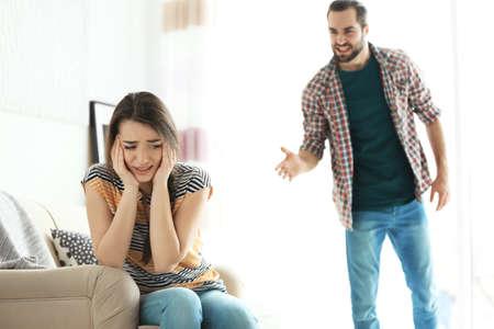 Jeune couple ayant une dispute dans le salon Banque d'images