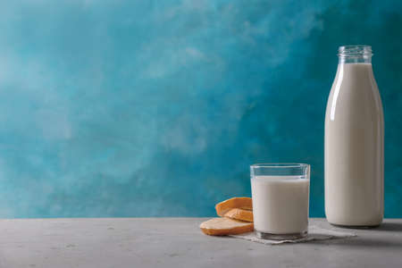 Glassware with milk and bread on table against color background
