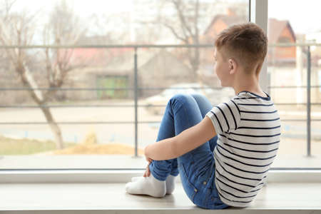 Lonely little boy sitting on windowsill. Autism concept