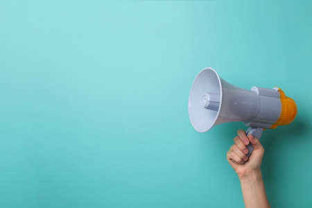 Man holding megaphone on color background Stock Photo