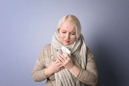 Mature woman with tissue suffering from cold on color background