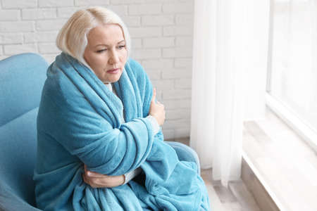 Mature woman wrapped in blanket suffering from cold at home