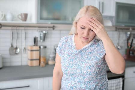 Mature woman suffering from headache in kitchen