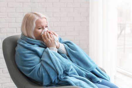 Mujer madura envuelta en una manta que sufren de frío en casa Foto de archivo
