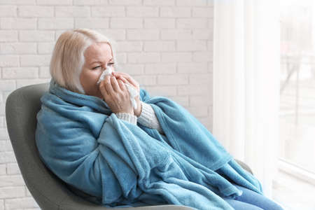 Reife Frau in Decke gewickelt, die zu Hause an Kälte leidet Standard-Bild