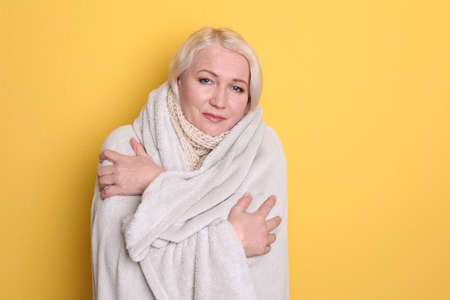 Mature woman wrapped in blanket suffering from cold on color background