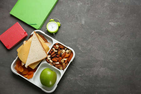 Flat lay composition with lunch box and appetizing food for school on grey background