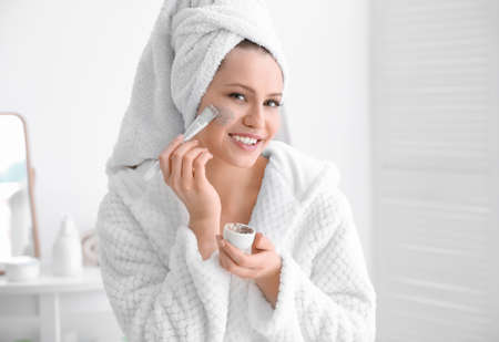 Mujer aplicando exfoliante en la cara en el baño.