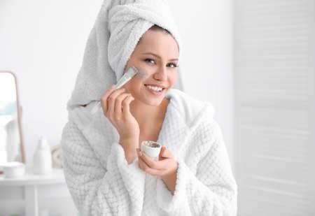 Woman applying scrub onto face in bathroom Imagens - 106969985