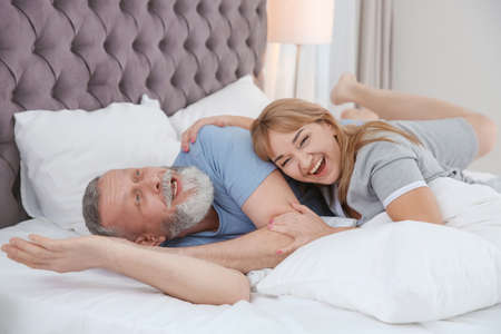 Mature couple having fun together on bed at home