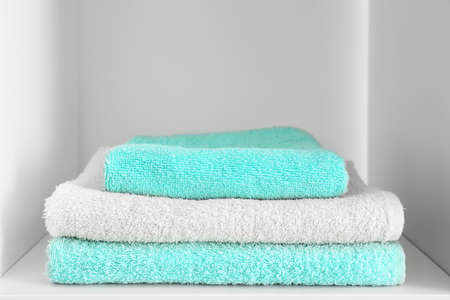 Stack of clean towels on shelf
