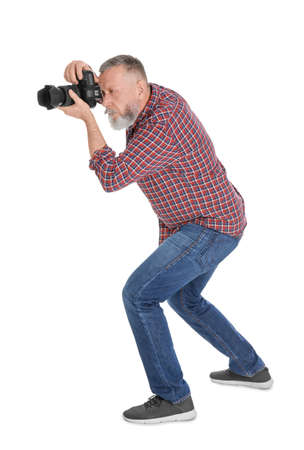 Mature male photographer with camera on white background