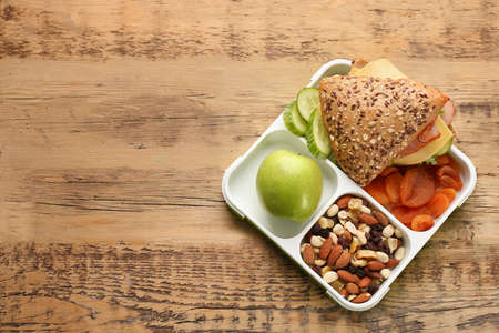 Lunch box with tasty food on wooden background Stock Photo