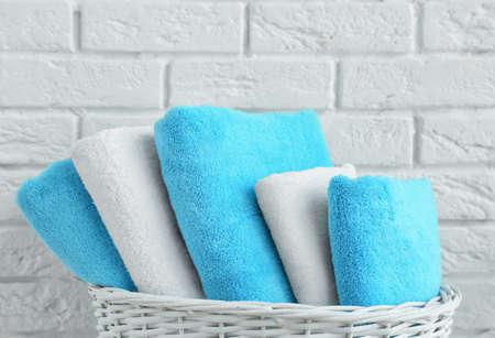 Wicker basket with clean towels in bathroom