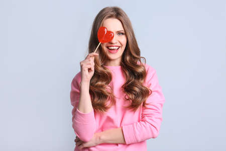 Portrait of young woman with long beautiful hair and lollipop on color background