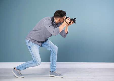 Male photographer with camera near grey wall Banco de Imagens
