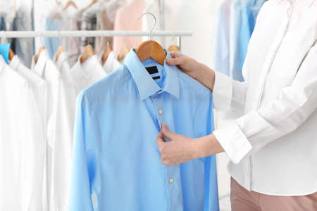 Mujer joven, tenencia, percha, con, camisa, en, tintorería Foto de archivo