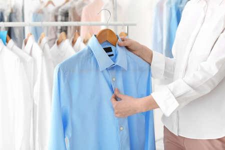 乾式掃除機でシャツを着たハンガーを持つ若い女性