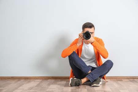 Male photographer with camera near light wall Stock Photo