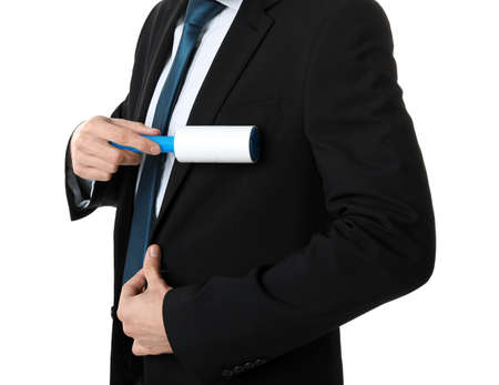 Young man cleaning jacket with lint roller on white background