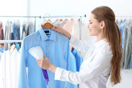 Mujer joven camisa humeante en la tintorería