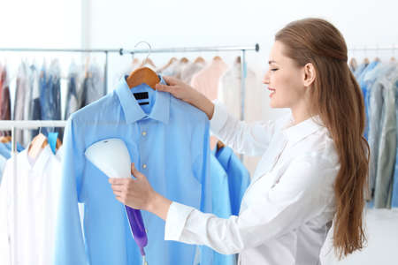 Young woman steaming shirt at dry-cleaner's