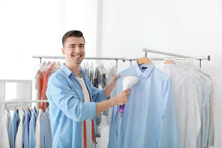 Young man steaming shirt at dry-cleaner's Stockfoto
