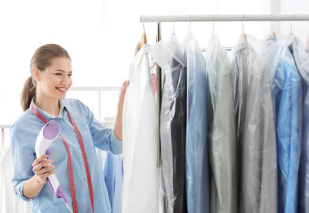 Young woman steaming shirt at dry-cleaners Imagens