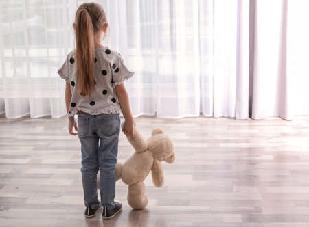 Lonely little girl with toy indoors. Autism concept