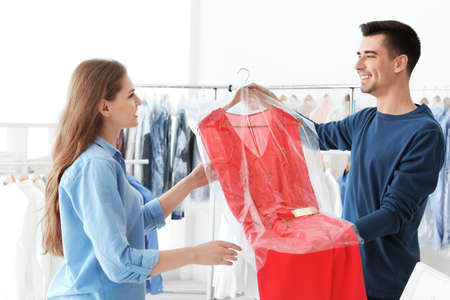 Young woman receiving her dress at dry-cleaner's Фото со стока
