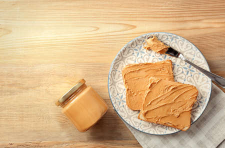 Jar with creamy peanut butter and toasts on plate