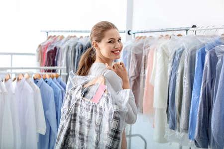 Junge Frau, die Kleiderbügel mit Kleidern in der Plastiktüte bei der Reinigung hält