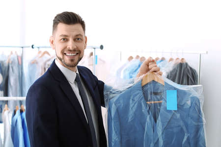 Young businessman holding hanger with jacket in plastic bag at dry-cleaner's