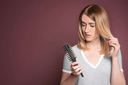 Young woman with hair loss problem on color background