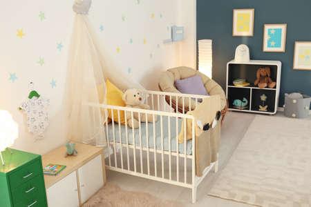 Stylish baby room interior with crib Stockfoto