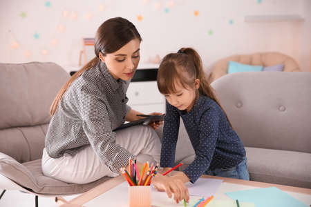 Female psychologist working with cute little girl in office Stock Photo